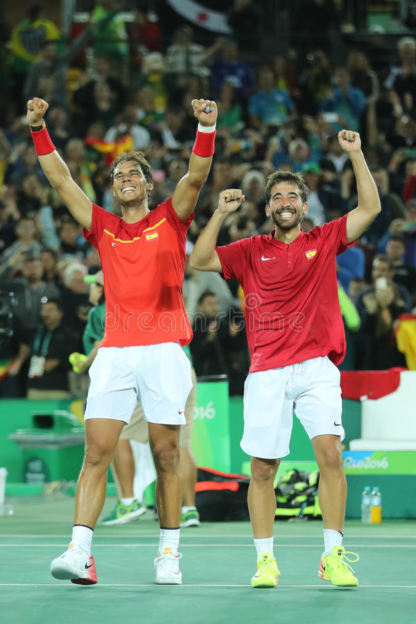 Los campeones olímpicos Rafael Nadal y Mark Lopez de España celebran la victoria en el final de los dobles de los hombres de la R imagen de archivo