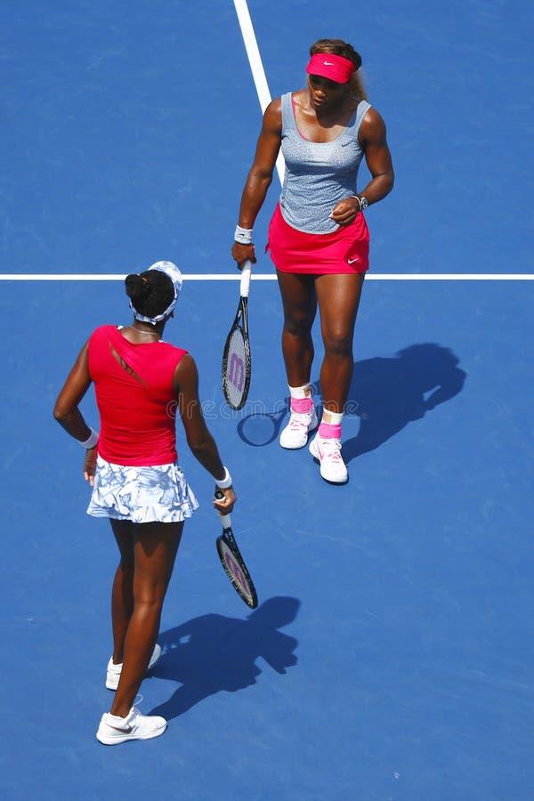 Los campeones Serena Williams y Venus Williams del Grand Slam durante dobles del cuarto de final hacen juego en el US Open 2014 fotografía de archivo libre de regalías