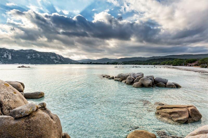 Los cantos rodados en un mar de la turquesa en Santa Giulia varan en Córcega fotografía de archivo