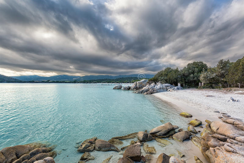 Los cantos rodados en un mar de la turquesa en Santa Giulia varan en Córcega imágenes de archivo libres de regalías