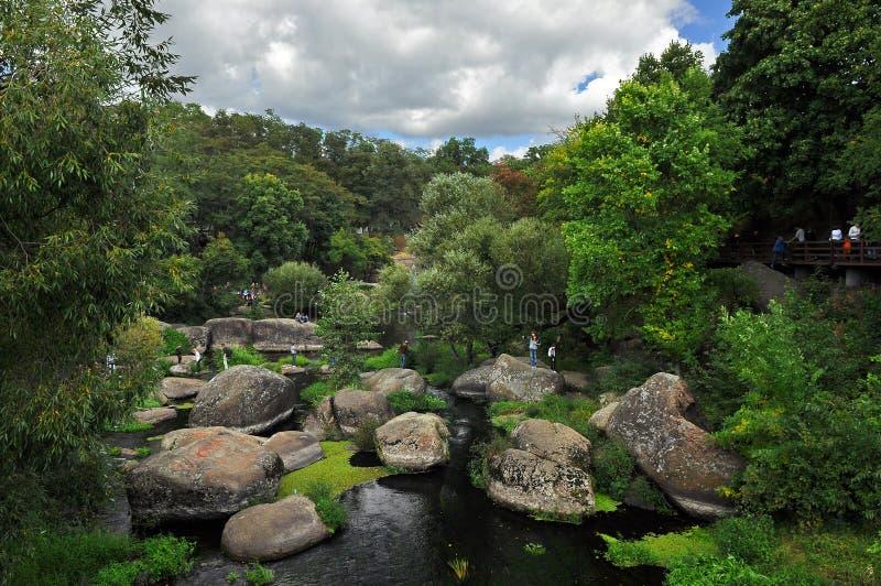 Los cantos rodados enormes mienten en el río entre altos árboles verdes contra el cielo azul foto de archivo libre de regalías