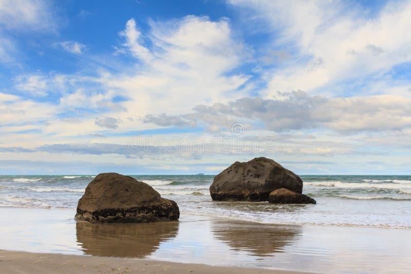 Los cantos rodados reflejaron en las arenas brillantes de una playa imágenes de archivo libres de regalías