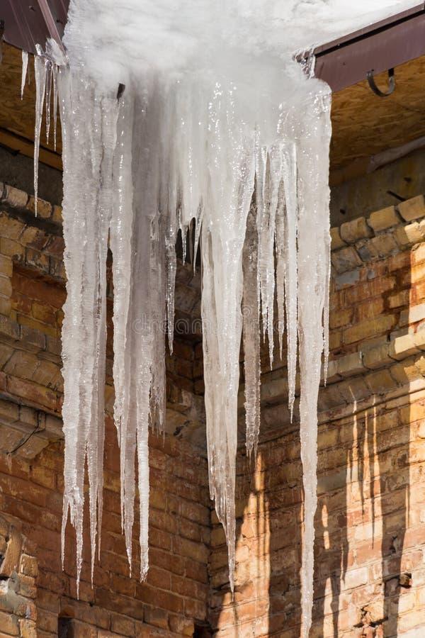 Los carámbanos cuelgan del tejado del edificio Invierno o día soleado de la primavera fotografía de archivo