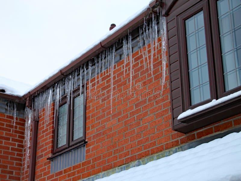 Los carámbanos largos cuelgan del canal de una casa El tejado se cubre en nieve y todavía está nevando fotos de archivo libres de regalías