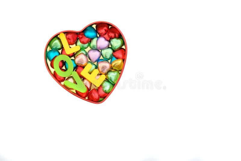 los caramelos de chocolate en diversos colores en una lata de la corazón-forma encajonan ingenio imágenes de archivo libres de regalías