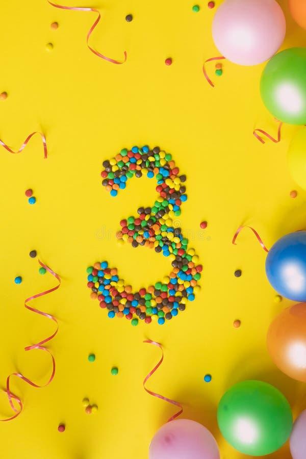 Los caramelos numeran 3 con los globos coloridos en fondo amarillo Concepto para los cumpleaños imagen de archivo