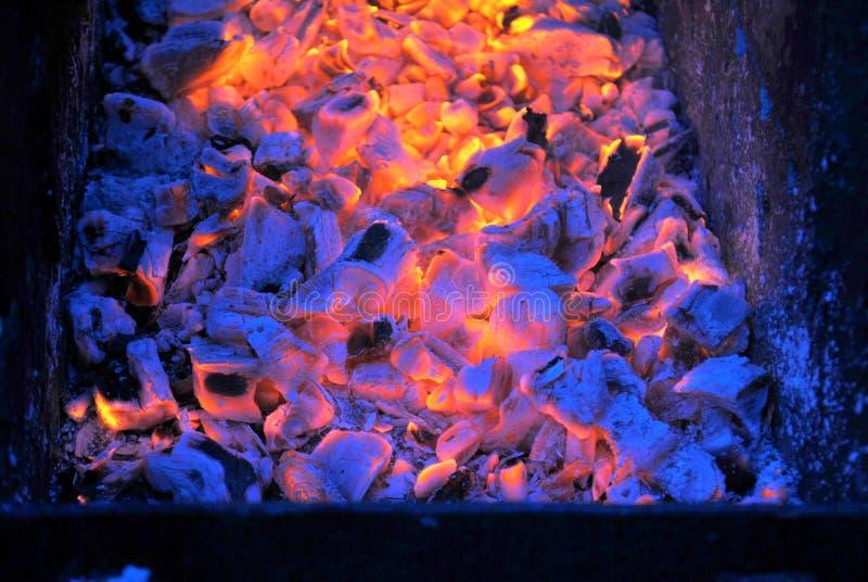 Los carbones calientes brillan intensamente en la oscuridad en la parrilla fotos de archivo libres de regalías