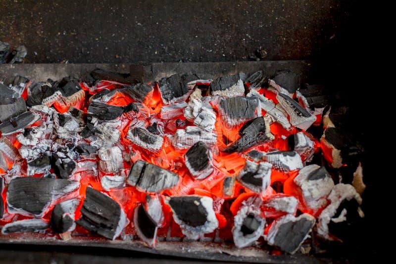 Los carbones calientes brillantes y el bosque ardiente en parrilla del Bbq marcan con hoyos El brillar intensamente y carb?n de l fotografía de archivo libre de regalías