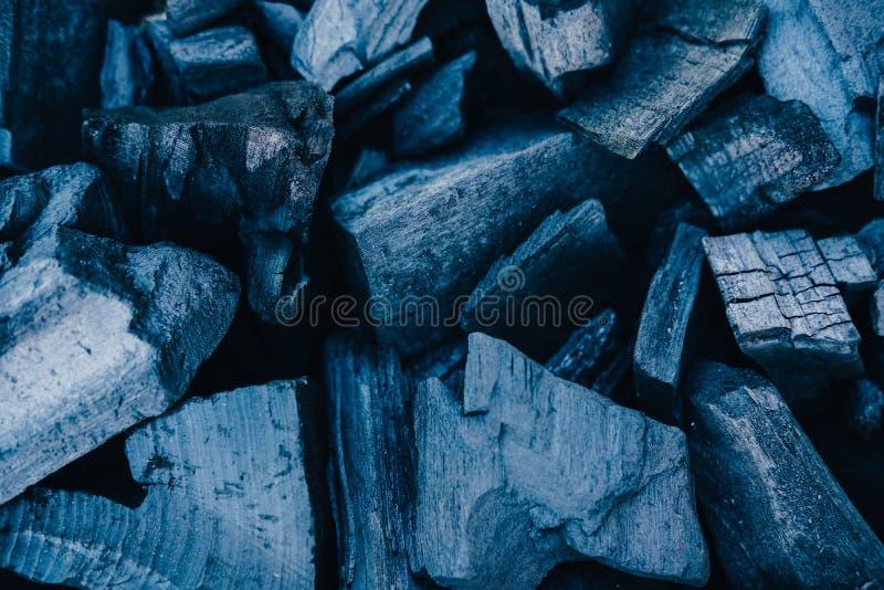 Los carbones negros se cierran encima de fondo imagenes de archivo