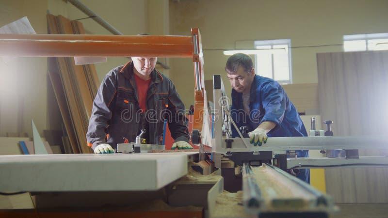 Los carpinteros de los trabajadores están cortando al tablero de madera en la sierra eléctrica en la fábrica de los muebles foto de archivo