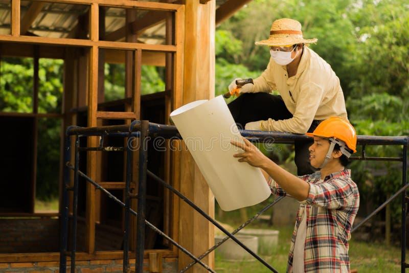 Los carpinteros están planeando construir un hogar imagenes de archivo