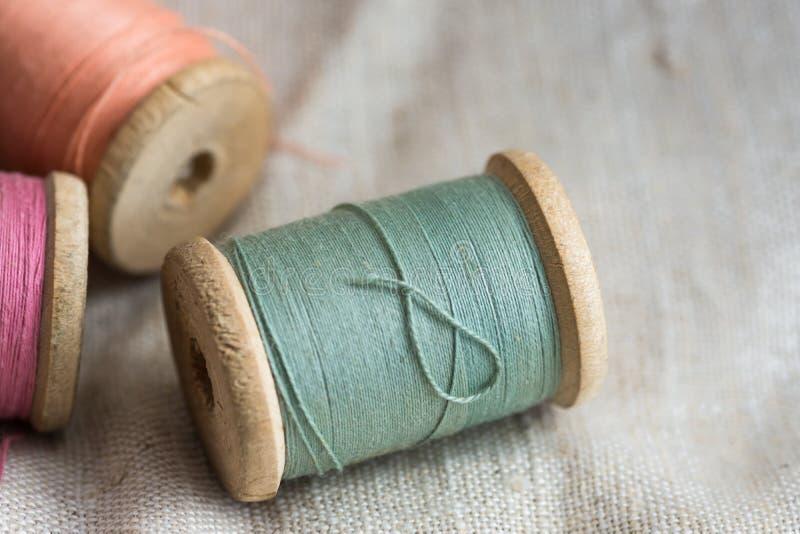 Los carretes de madera en el paño de lino, colores en colores pastel, primer del hilo de VVintage, diseñaron imagen imagenes de archivo