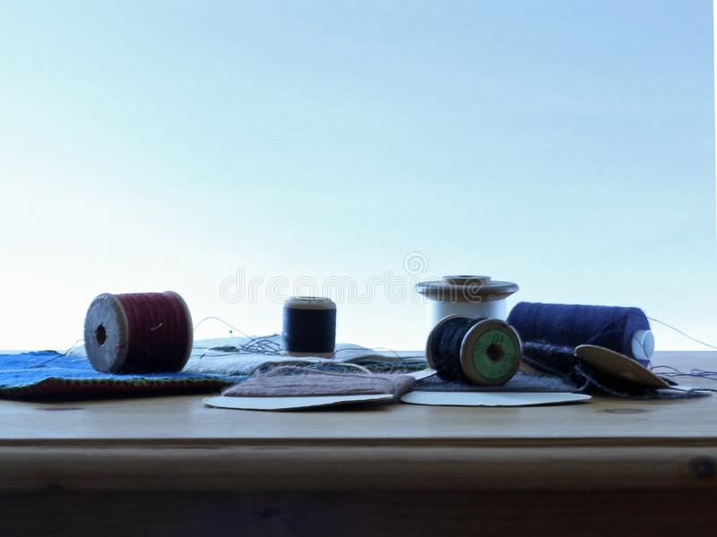 Los carretes del algodón se cierran para arriba en una tabla con un fondo azul claro fotos de archivo libres de regalías
