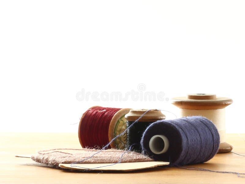 Los carretes del algodón se cierran para arriba en una tabla con un fondo blanco fotografía de archivo libre de regalías