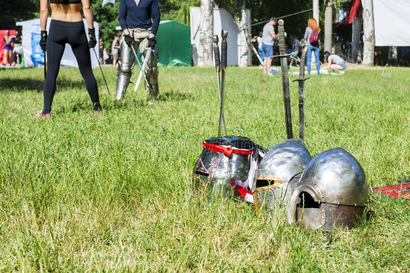 Los cascos caballerescos mienten en la hierba contra la perspectiva de gente espada-que lucha foto de archivo