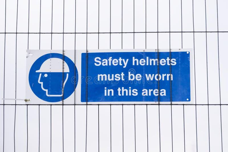 Los cascos de los cascos de seguridad deben ser muestra llevada en el emplazamiento de la obra fotografía de archivo