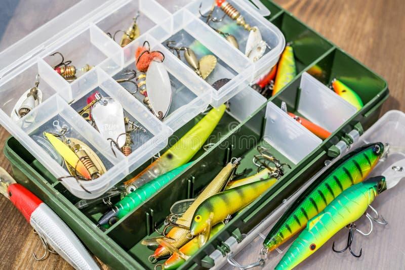 Los cebos de cuchara, engañan, las moscas, trastos en la caja para coger o pescar un pescado depredador en fondo de madera de la  fotografía de archivo libre de regalías