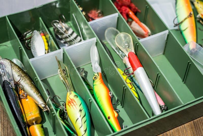Los cebos de cuchara, engañan, las moscas, trastos en la caja para coger o pescar un pescado depredador en fondo de madera de la  foto de archivo