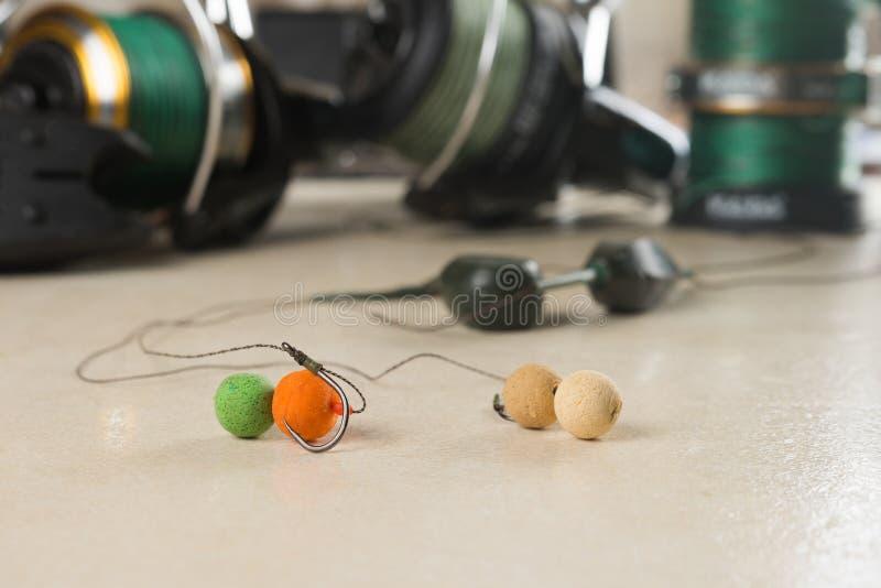 Los cebos, ganchos, plomos, carretes, se están preparando para la pesca de la carpa Copie la goma fotos de archivo