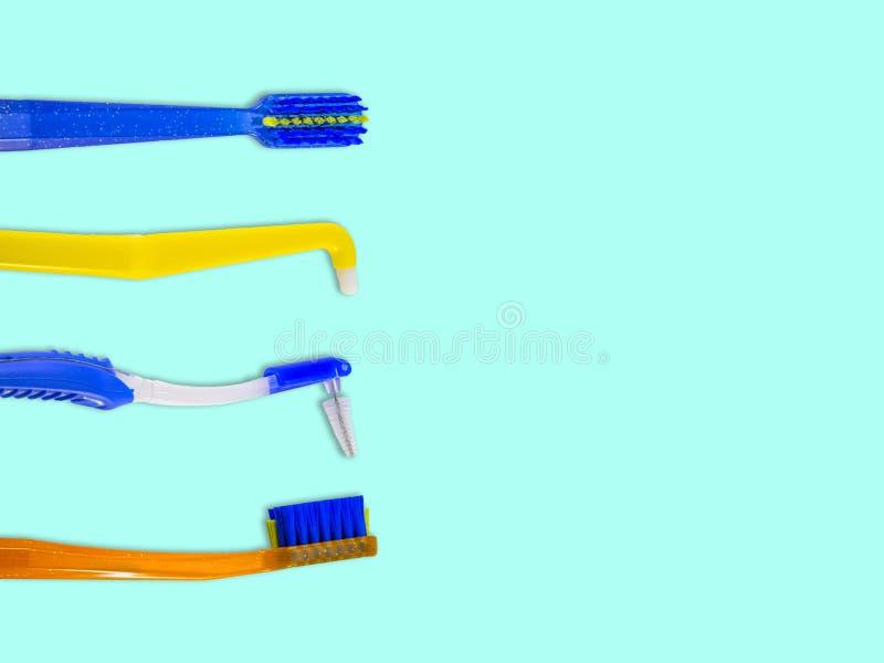 Los cepillos de dientes especiales para el cuidado de apoyos acorchetan los sistemas, en fila, aislados en un fondo azul claro, v fotos de archivo