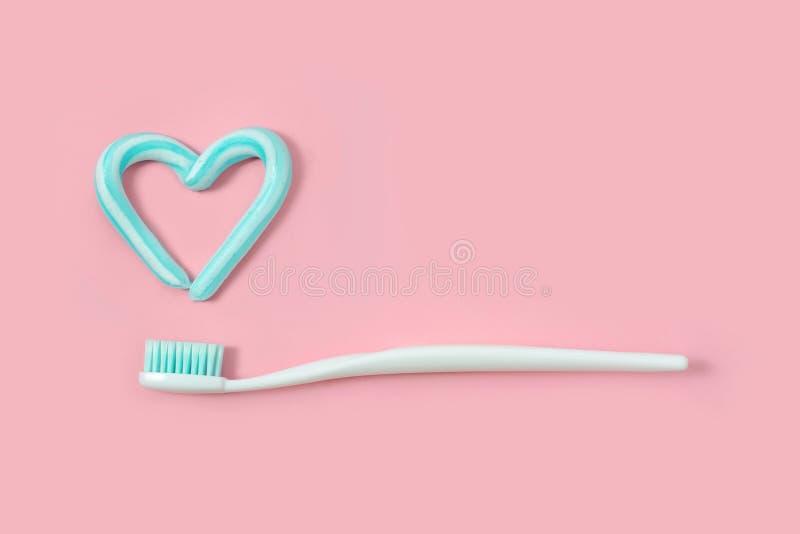 Los cepillos de dientes y la turquesa colorean la crema dental en la forma del corazón en fondo rosado Concepto dental y de la at fotos de archivo