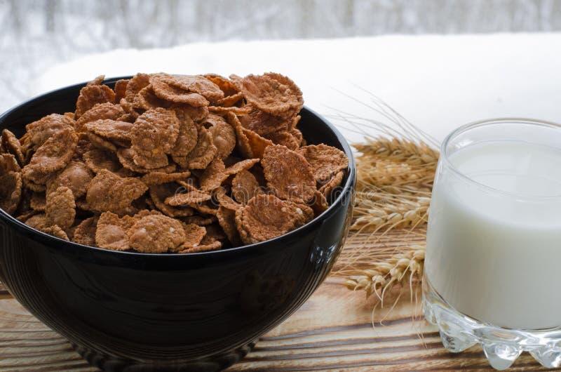 Los cereales de un desayuno sanos están en la placa negra en el fondo de madera fotos de archivo