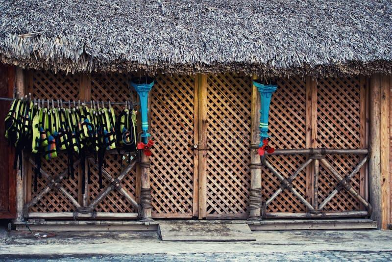 Los chalecos salvavidas cuelgan en la entrada a la tienda La fachada de la estructura de madera imagenes de archivo