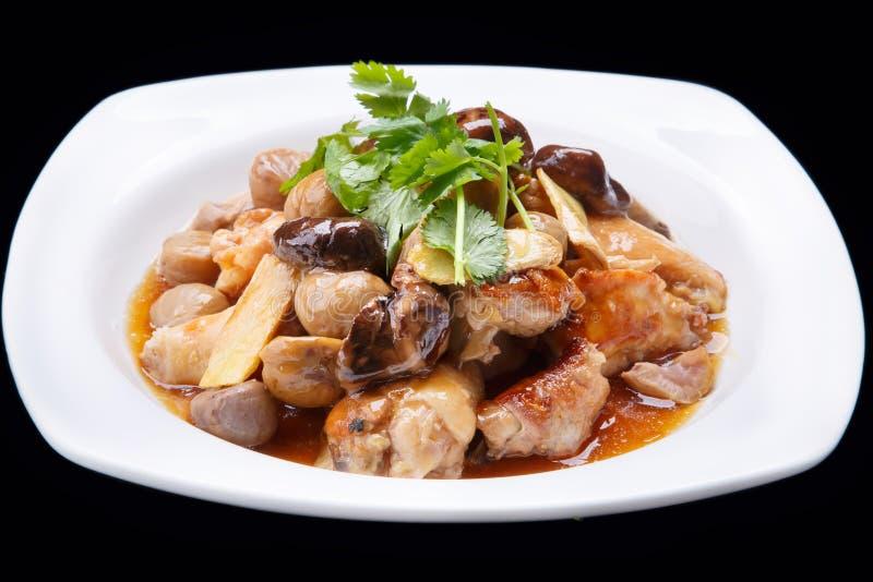 Los chinos sofríen el pollo y la seta aislados en el fondo negro, cocina china foto de archivo