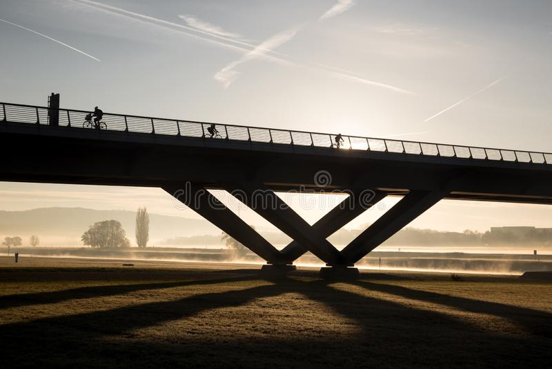 Los ciclistas montan por la mañana en niebla y la salida del sol sobre un puente fotografía de archivo