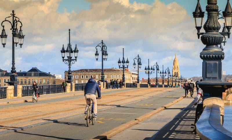 Los ciclistas y los peatones dan un paseo en el puente del río de Burdeos imagen de archivo libre de regalías