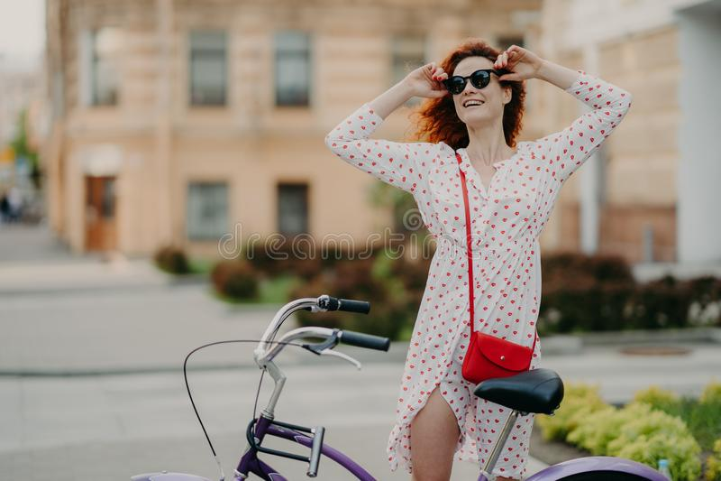 Los ciclos despreocupados felices de la mujer en ciudad, presentan cerca de la bicicleta, mantienen las manos en las sombras, ves imagen de archivo libre de regalías