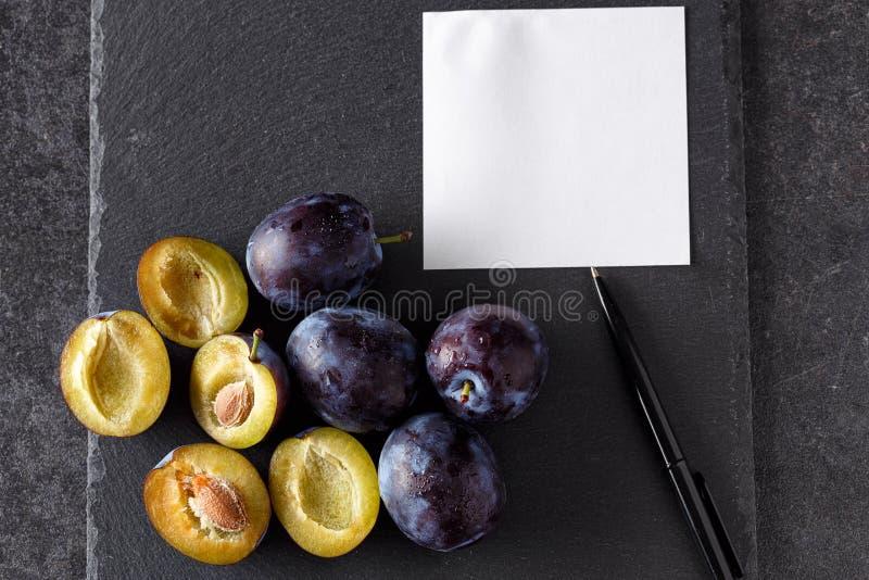 Los ciruelos, entero y las rebanadas con el papel en blanco - añada para poseer el texto foto de archivo libre de regalías