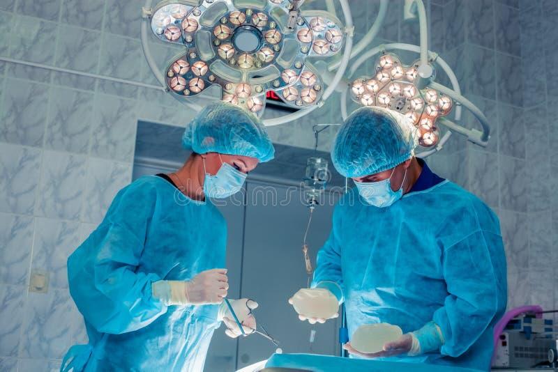Los cirujanos combinan el trabajo con la supervisión del paciente en ope quirúrgico imagen de archivo libre de regalías