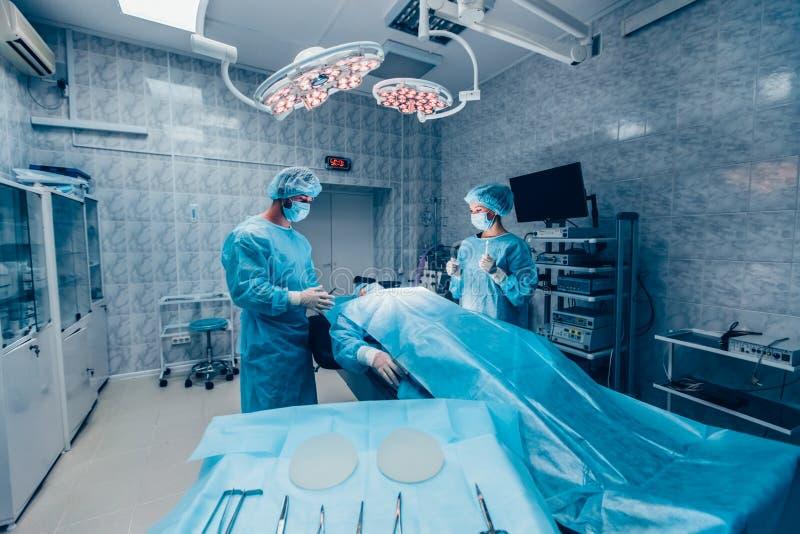 Los cirujanos combinan el trabajo con la supervisión del paciente en quirúrgico imagen de archivo libre de regalías