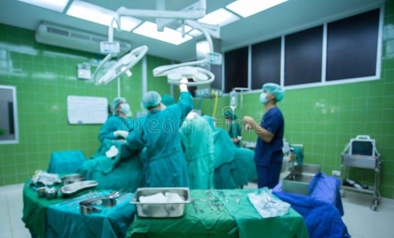 Los cirujanos combinan el trabajo con la supervisión del paciente en sala de operaciones quirúrgica imagen de archivo