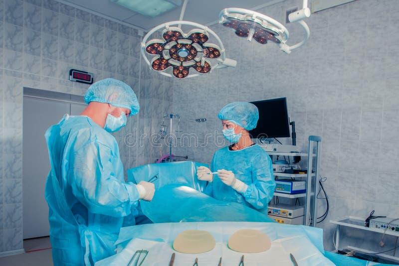 Los cirujanos combinan el trabajo con la supervisión del paciente en sala de operaciones quirúrgica Aumento del pecho fotos de archivo