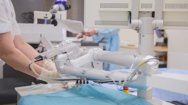 Los cirujanos y el anesthesiologist se preparan para la cirugía en una sala de operaciones - oftalmología imagenes de archivo
