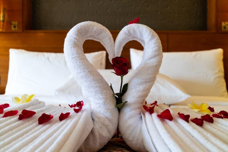 Los cisnes de la papiroflexia hicieron fuera de las toallas y presentado en una cama en una habitación nupcial imágenes de archivo libres de regalías