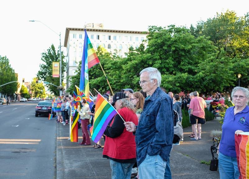 Los ciudadanos diversos sostienen banderas del arco iris en la vigilia de Corvallis para las muertes del tiroteo de Orlando imágenes de archivo libres de regalías