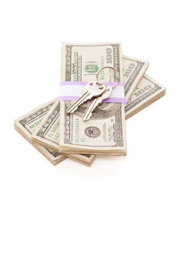 Los claves de la casa en la pila de dinero aislaron fotografía de archivo
