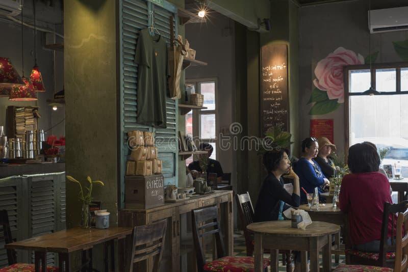 Los clientes disfrutan de un momento en Cong Ca Phe en Ho Chi Minh City, Vietnam fotos de archivo libres de regalías