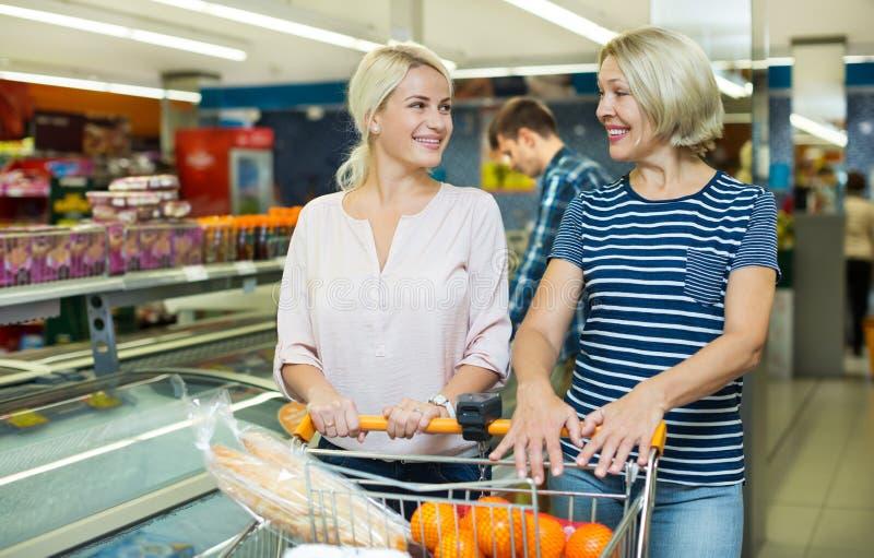 Los clientes femeninos cerca exhiben con la comida congelada imágenes de archivo libres de regalías