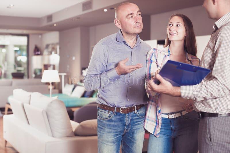 Los clientes jovenes están consultando con el vendedor para elegir el nuevo sofá foto de archivo libre de regalías
