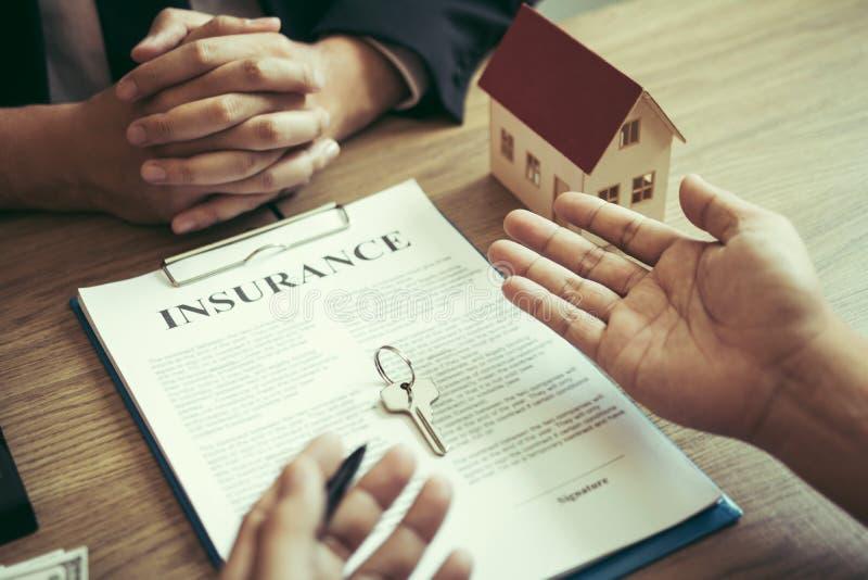Los clientes que compran casas están negociando con los agentes el costo del seguro de vivienda imagen de archivo
