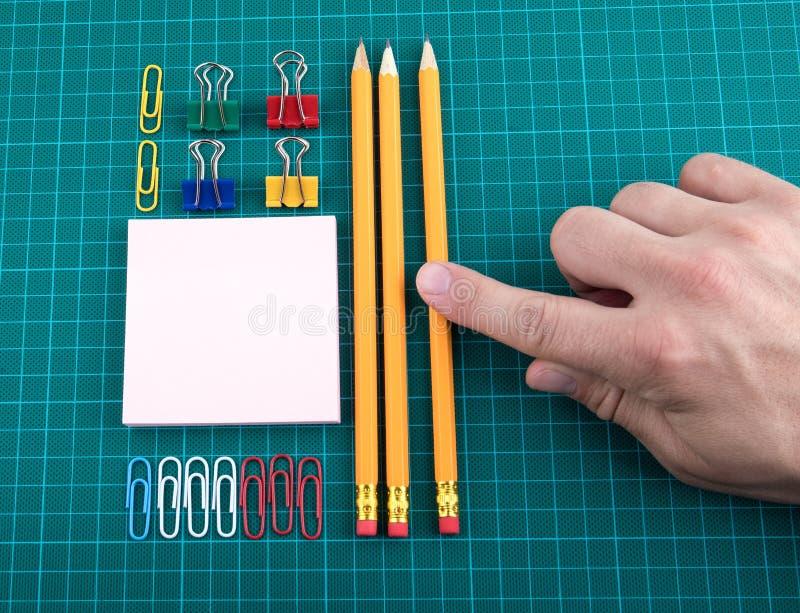 Los clips de papel, los lápices y la nota cubren en backgound verde comprobado fotografía de archivo