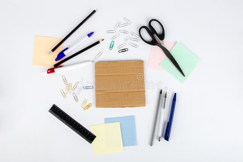 Los clips de papel y la cartulina de la etiqueta engomada del lápiz de la pluma de las tijeras mienten en la tabla Visión desde a imagenes de archivo