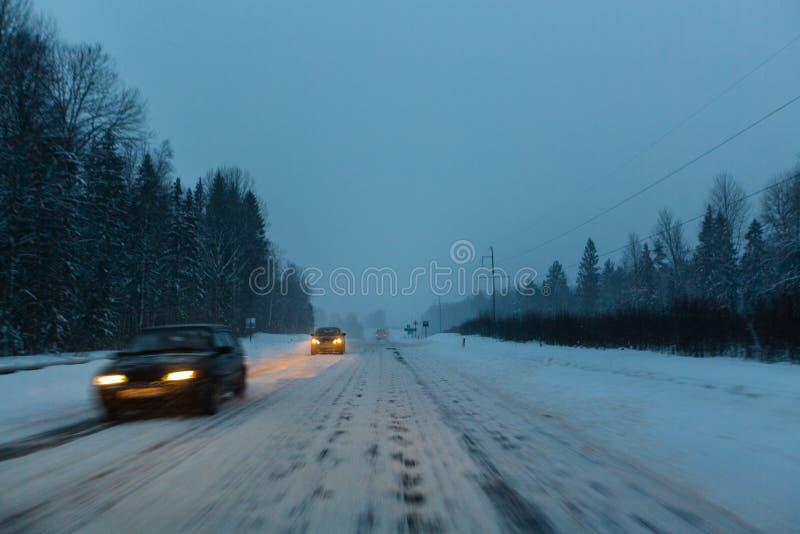 Los coches conducen con las linternas en el camino del invierno en una tormenta de la nieve en el crepúsculo cuando la nieve está imagen de archivo