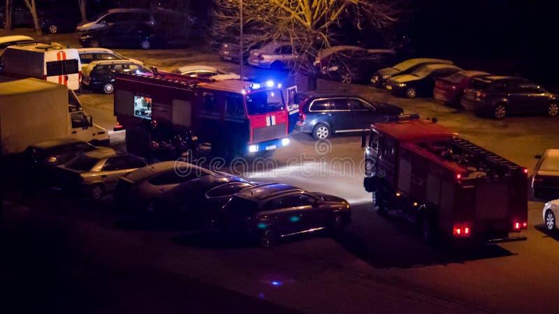 Los coches de bomberos están en el camino con las luces que destellan prendido en la noche fotos de archivo