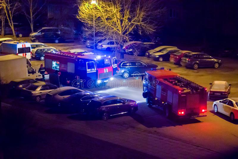Los coches de bomberos est?n en el camino con las luces que destellan prendido en la noche imágenes de archivo libres de regalías