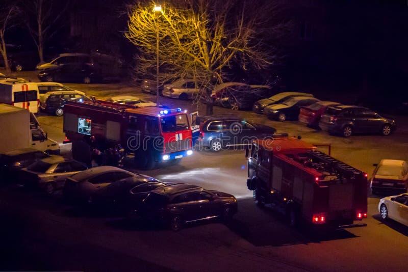 Los coches de bomberos est?n en el camino con las luces que destellan prendido en la noche fotos de archivo